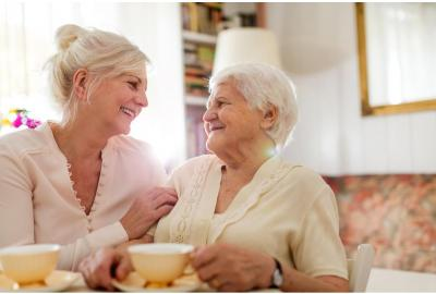 Senior woman & her daughter sitting in living room together, embracing & smiling over tea.