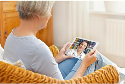 Person sitting on couch, holding tablet with doctor on screen conducting telehealth visit