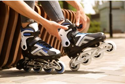 Person strapping up their white and black roller blades