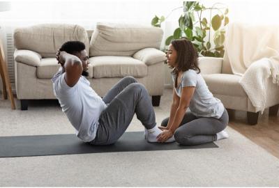woman helping man do sit ups