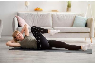 Elderly woman stretching on a floor mat
