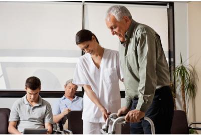 Caretaker helping elderly man using a walking aid