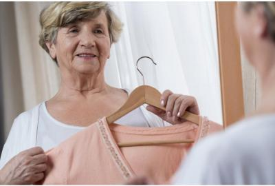 older woman holding up shirt on hanger