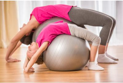 mom and daughter stretching on ball