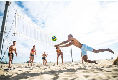 Group of people playing beach volleyball on sunny day.