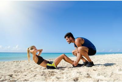 Woman doing sit up exercise on the beach while a partner holds her feet in place on the sand.