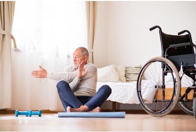 Elderly man sitting on yoga mat stretching