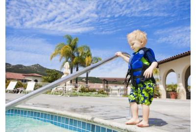 child standing beside pool