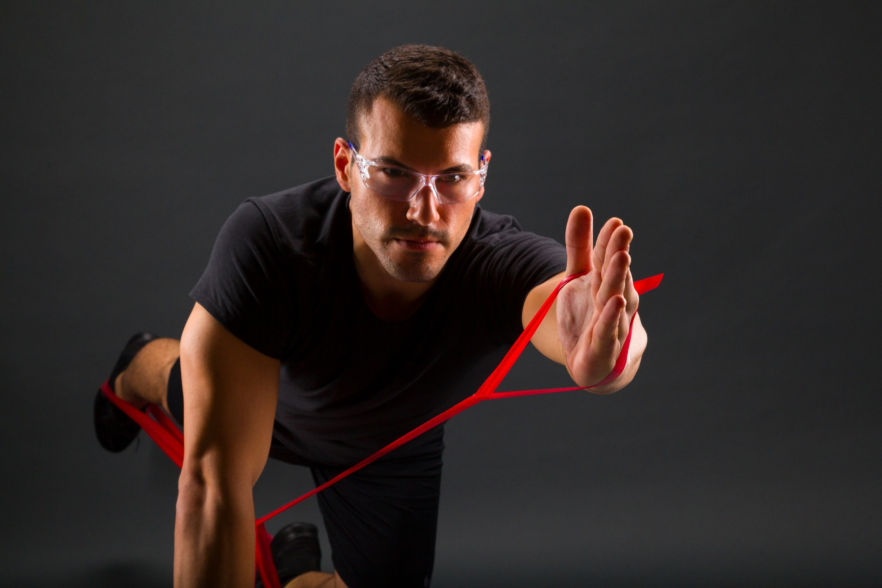 Man working out using a red TheraBand in medium resistance