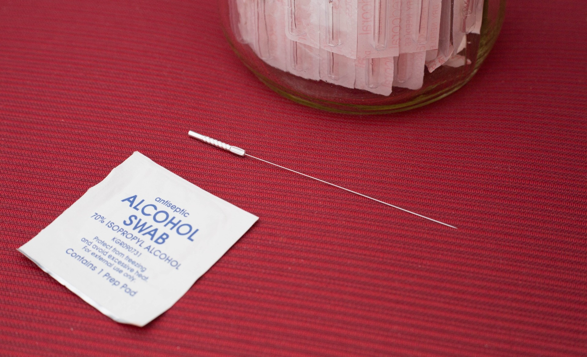 Photo of an alcohol swap packet next to a dry needling needle