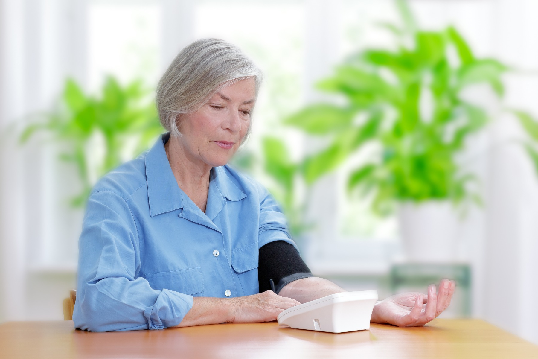 Senior woman sitting at table using a blood pressure monitor