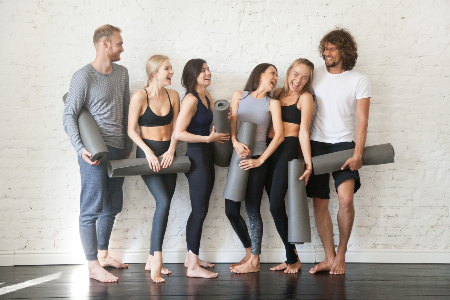 Group of yogis posed against a white brick wall holding yoga mats and smiling