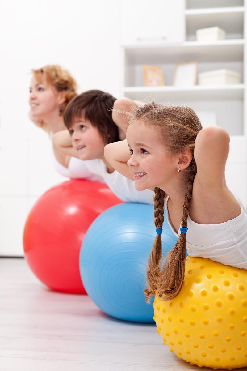 children doing supermans on exercise ball