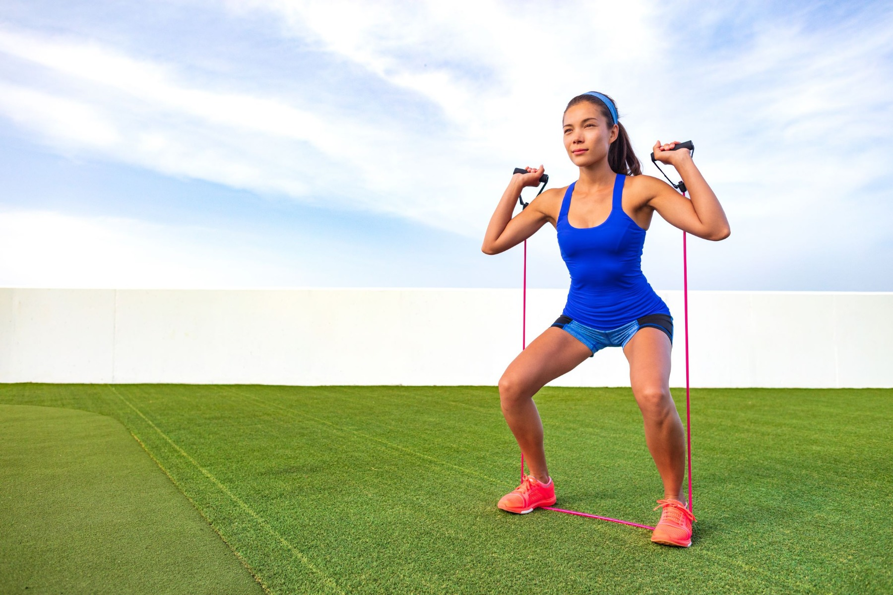 Woman standing in squat position holding resistance band, in overhead press stance