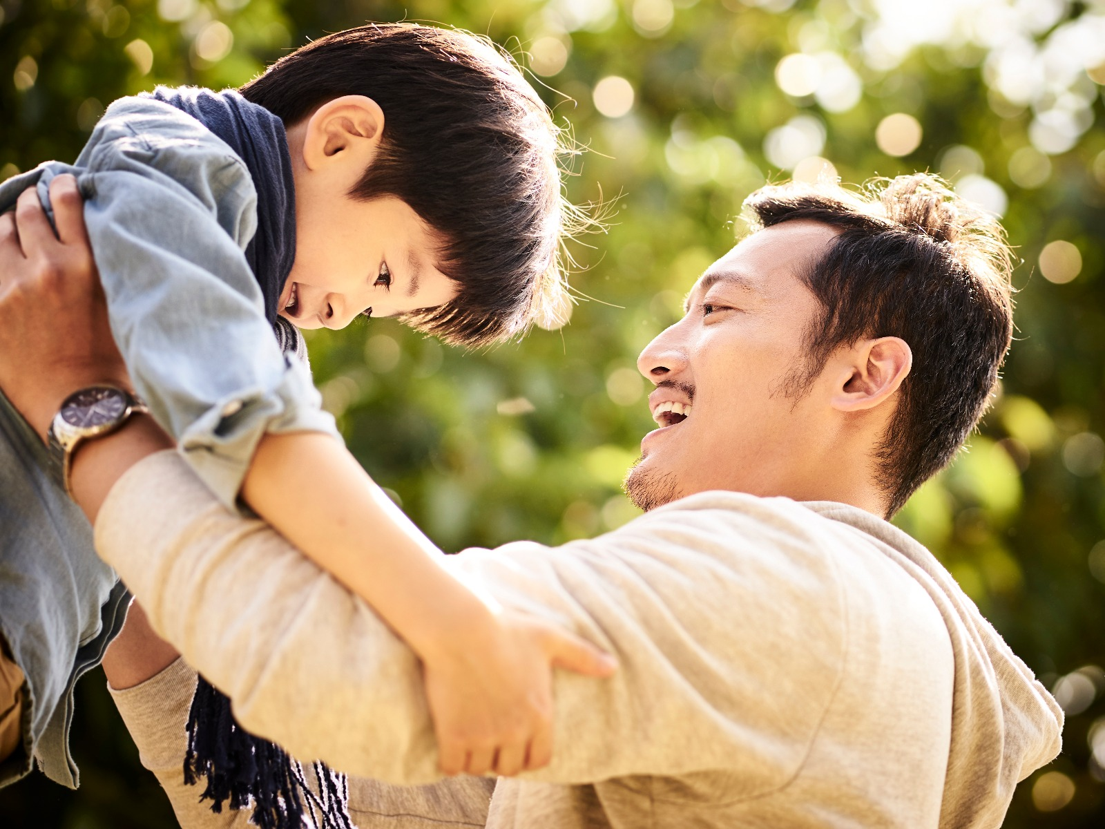 Father holding up his young son outside, both of them smiling and having fun