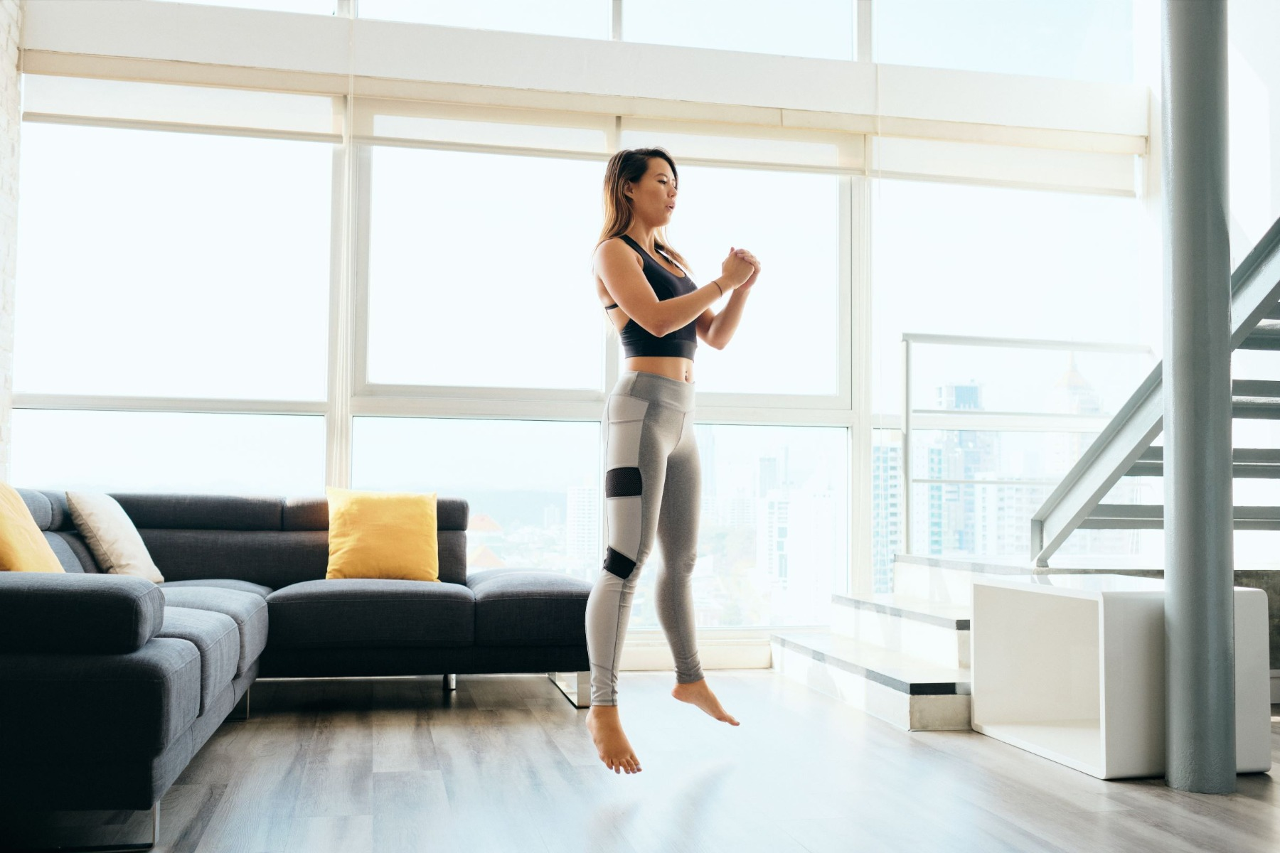 Woman doing jump squats in living room