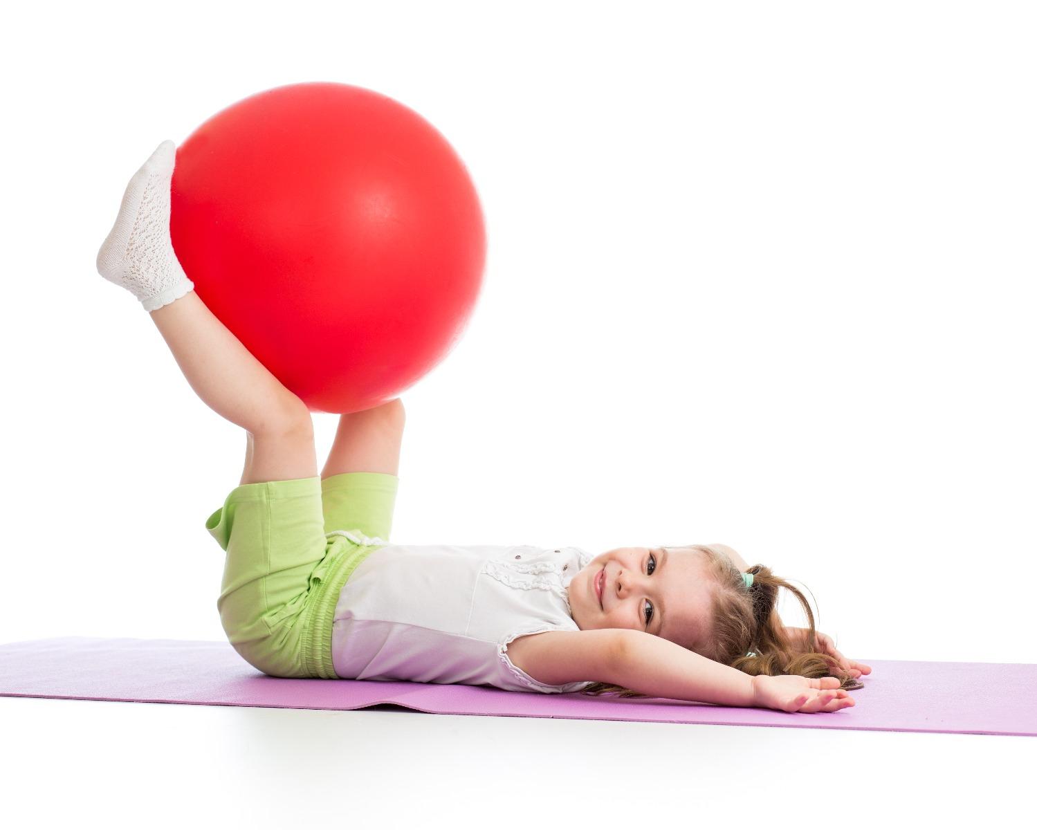little girl doing core exercises on exercise ball