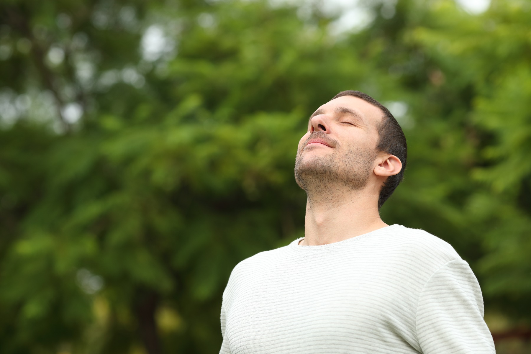 Man standing outside, looking up towards the sky peacefully with a smile on his face