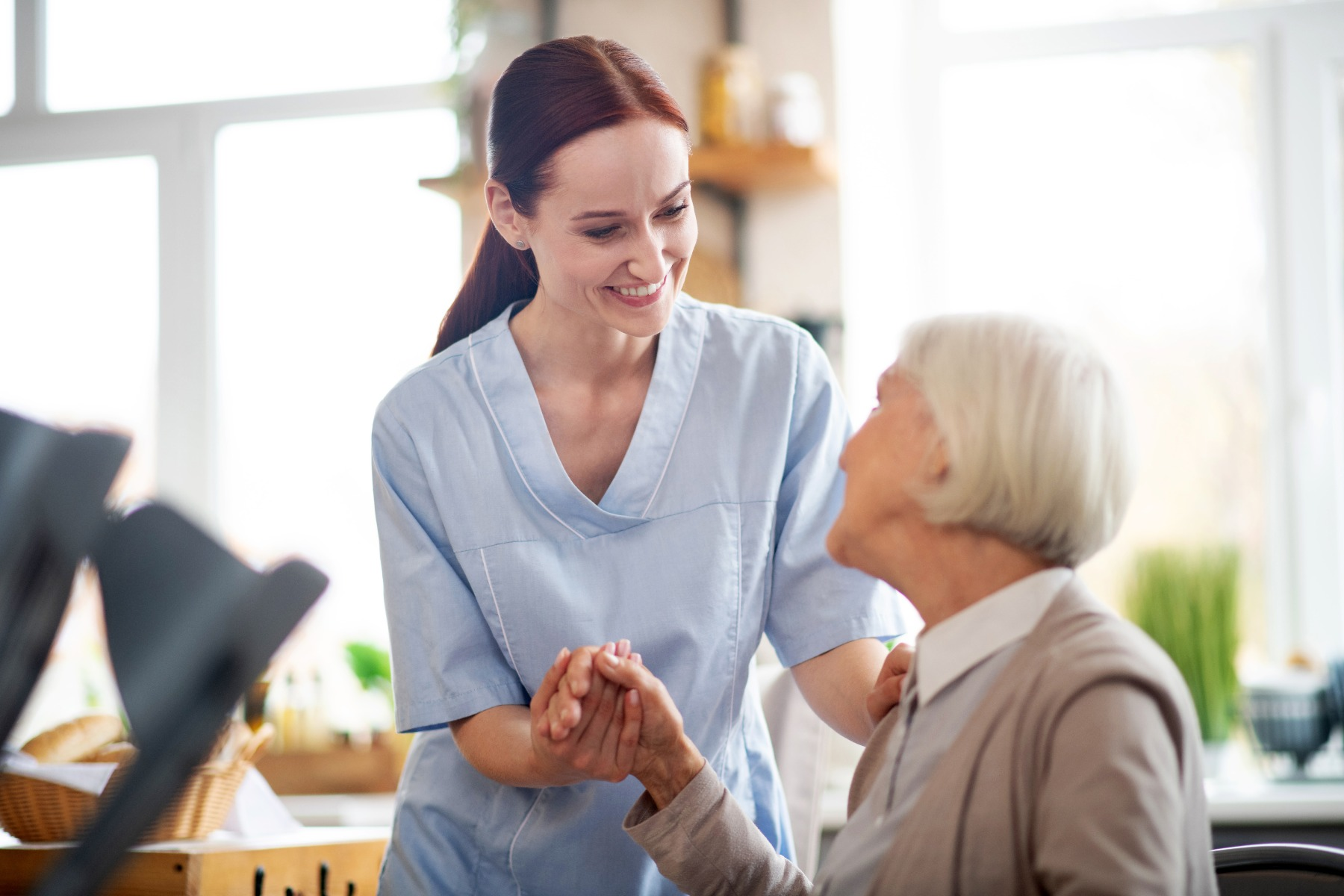 nurse helping elder woman