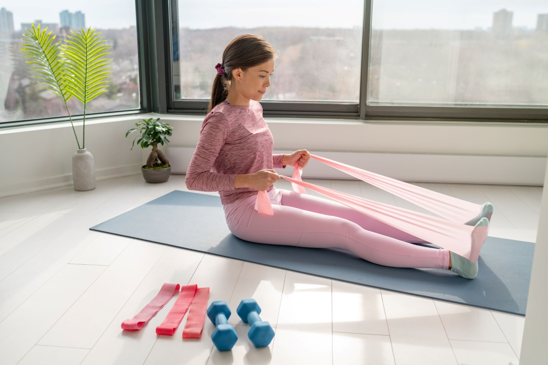 Woman sitting on mat doing row exercise with resistance band