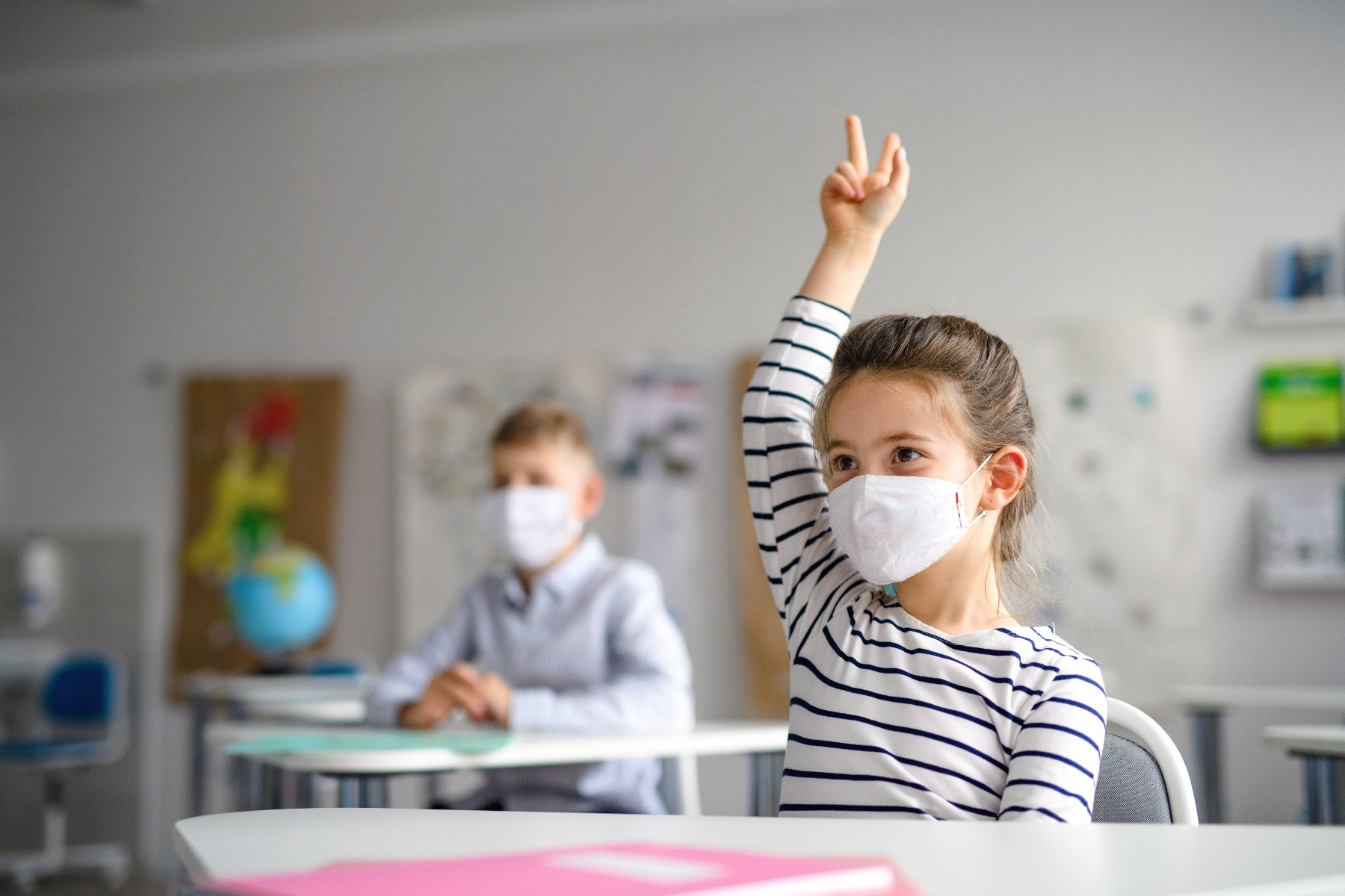 young girl in class raising hand with mask on