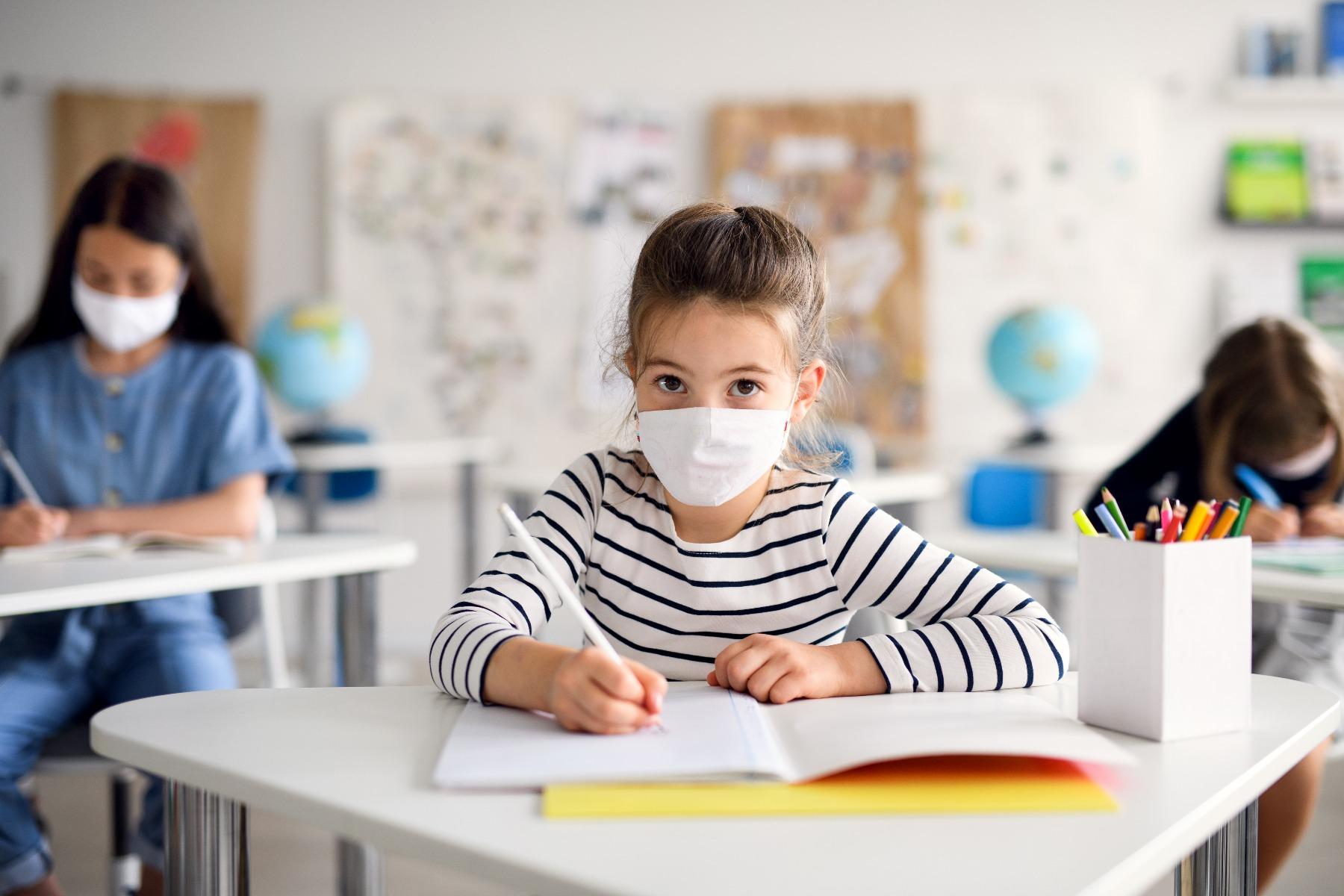 little girl writing in class