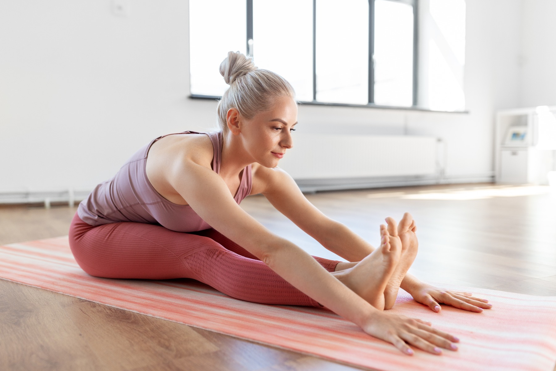 Seated woman on yoga mat stretching into forward fold