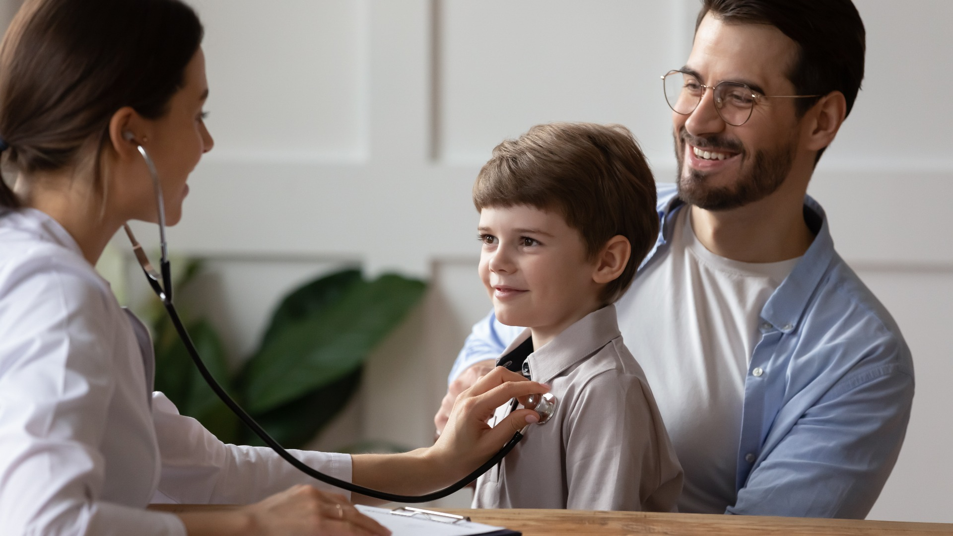Young boy held by his dad as a Doctor examines him with her stethoscope