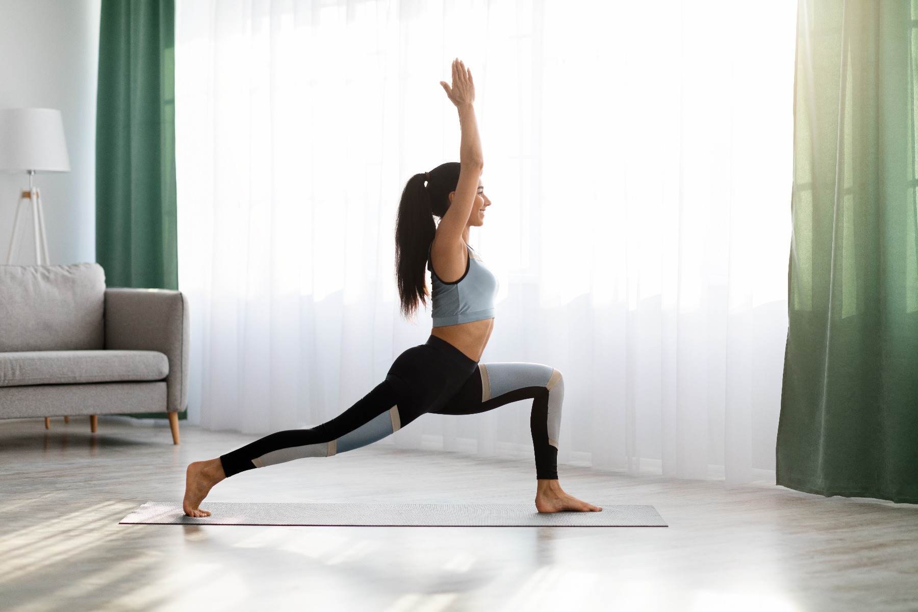 Woman standing on mat in warrior yoga pose