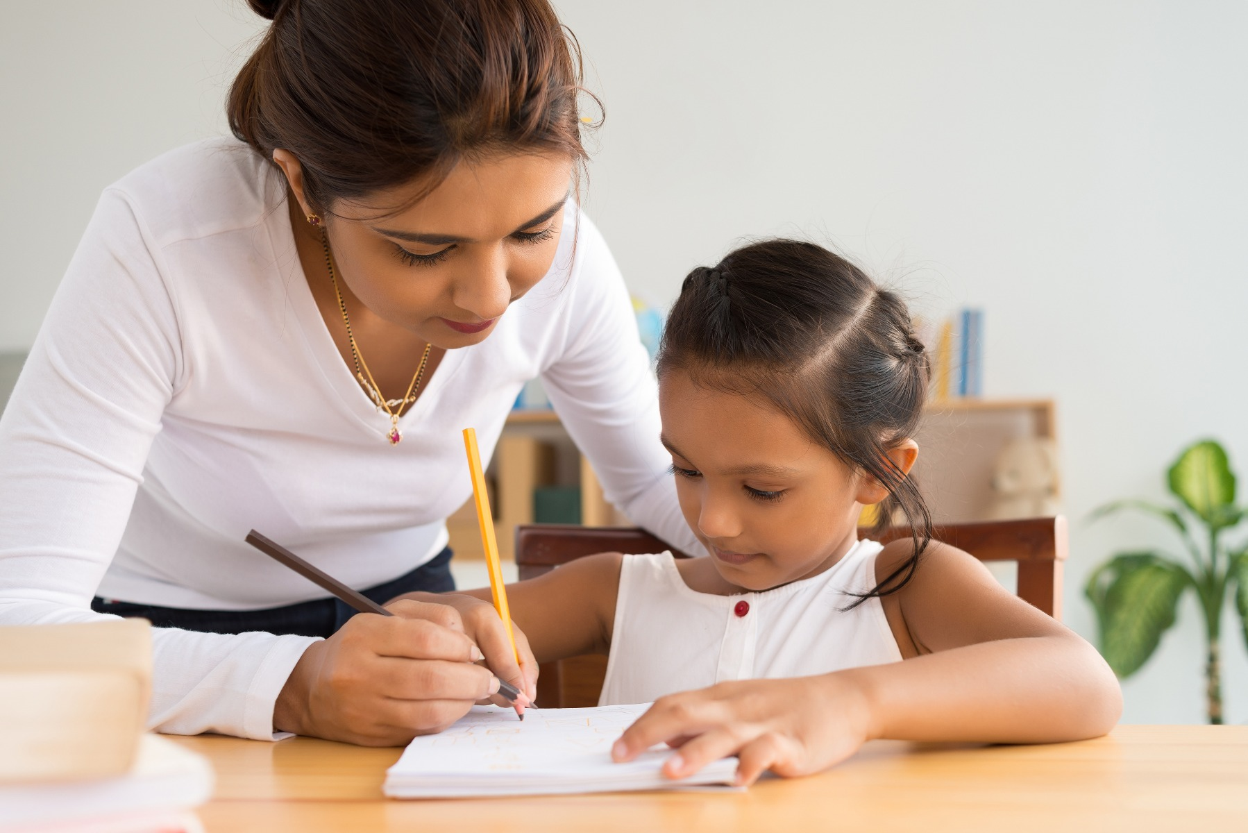 mother and little daughter writing together
