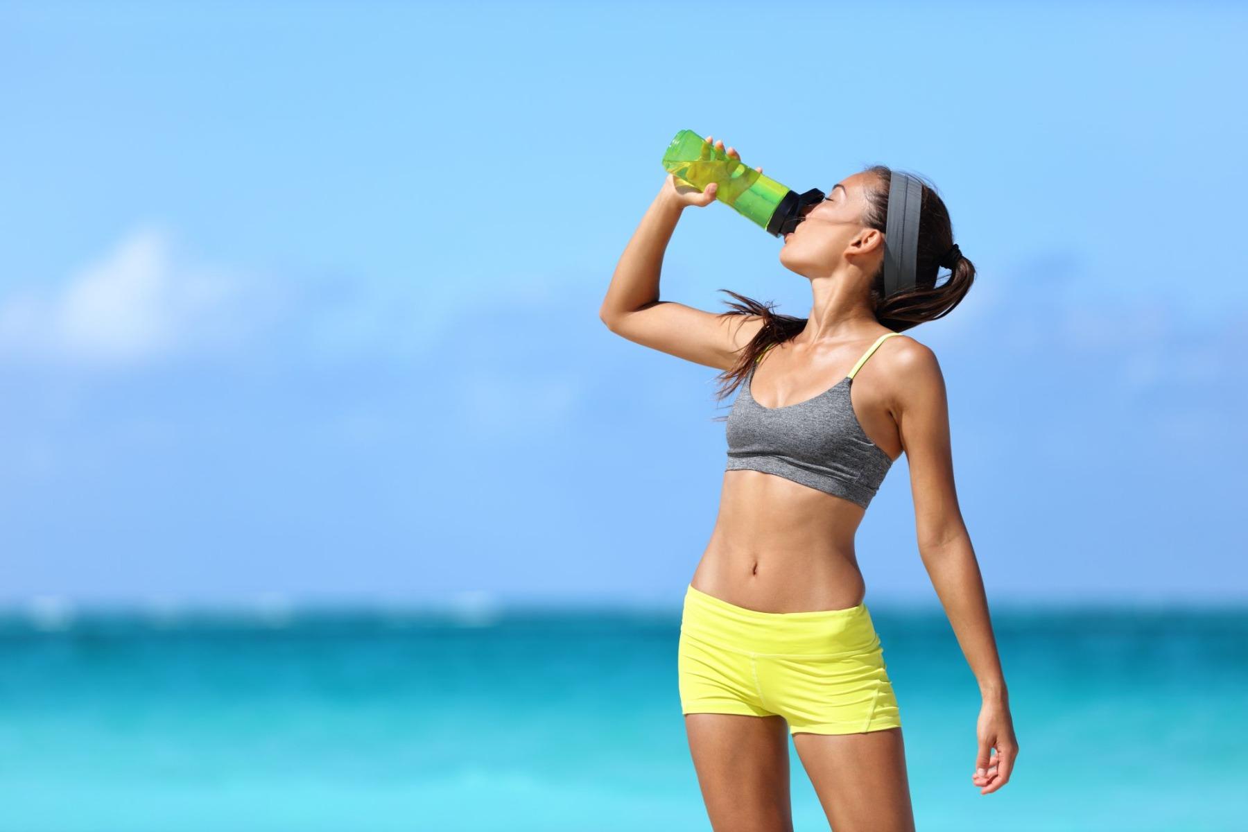 Woman in workout gear standing on beach drinking water from water bottle