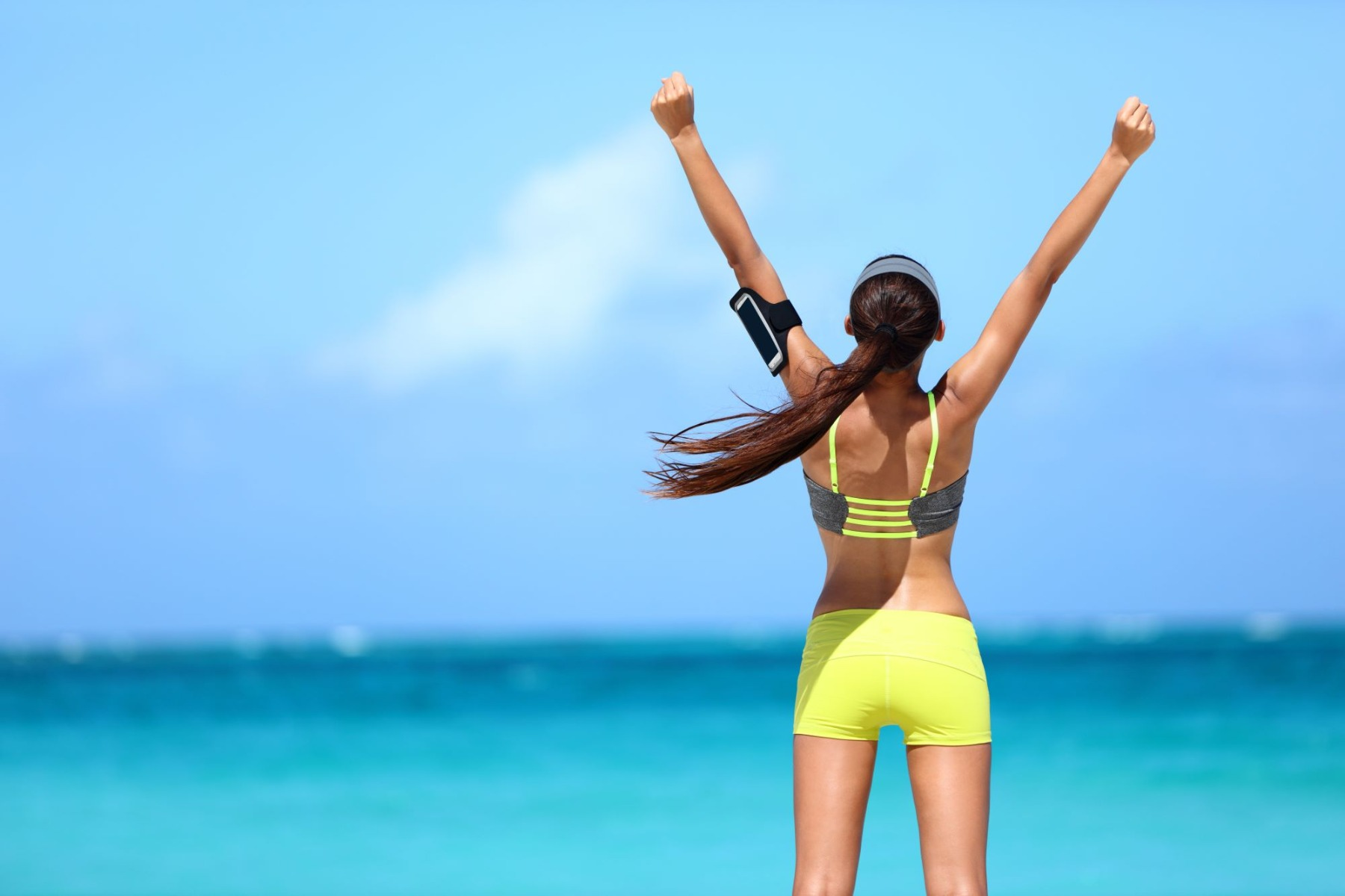 Woman in workout gear with back to camera standing on beach with arms raised up excitedly