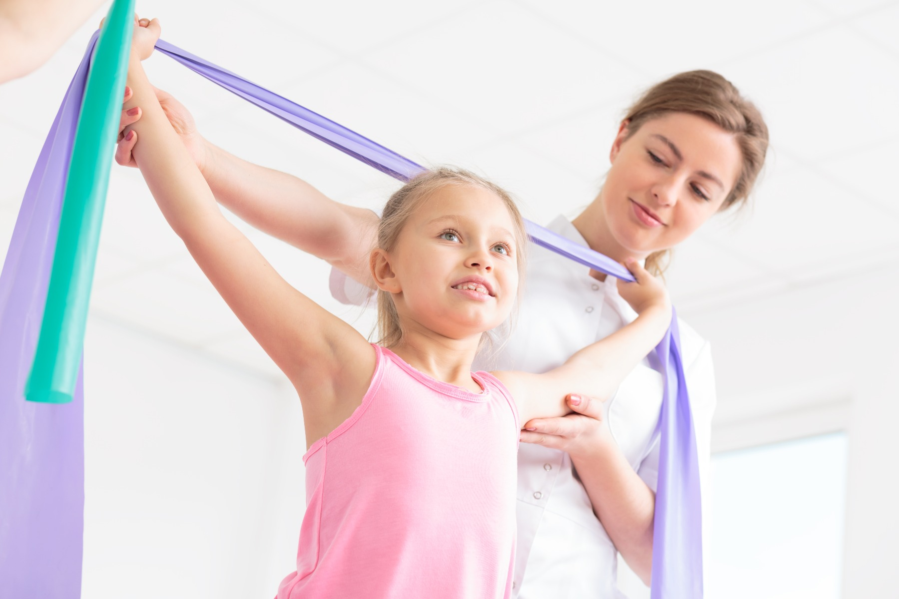 woman helping girl stretch with stretch bands