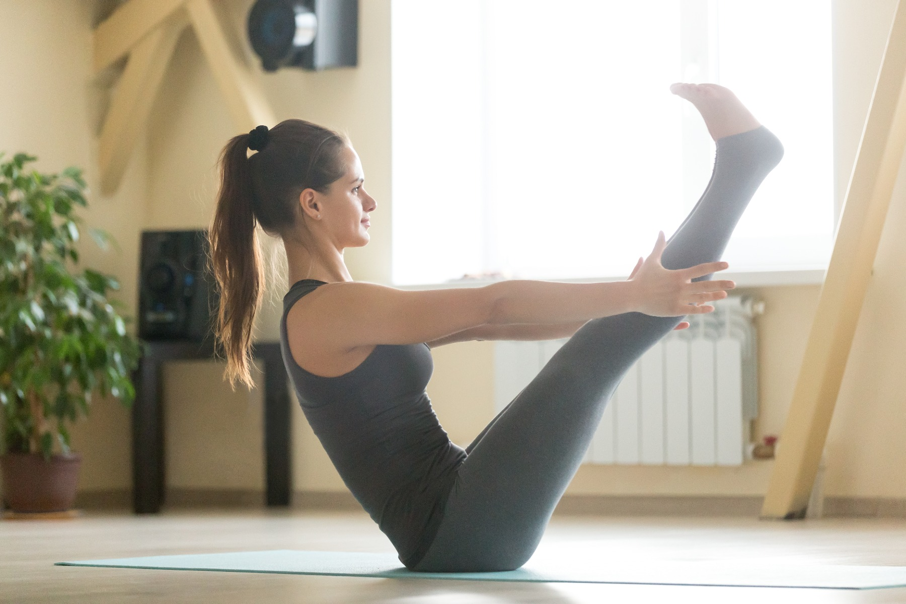 Woman on yoga mat in a boat pose