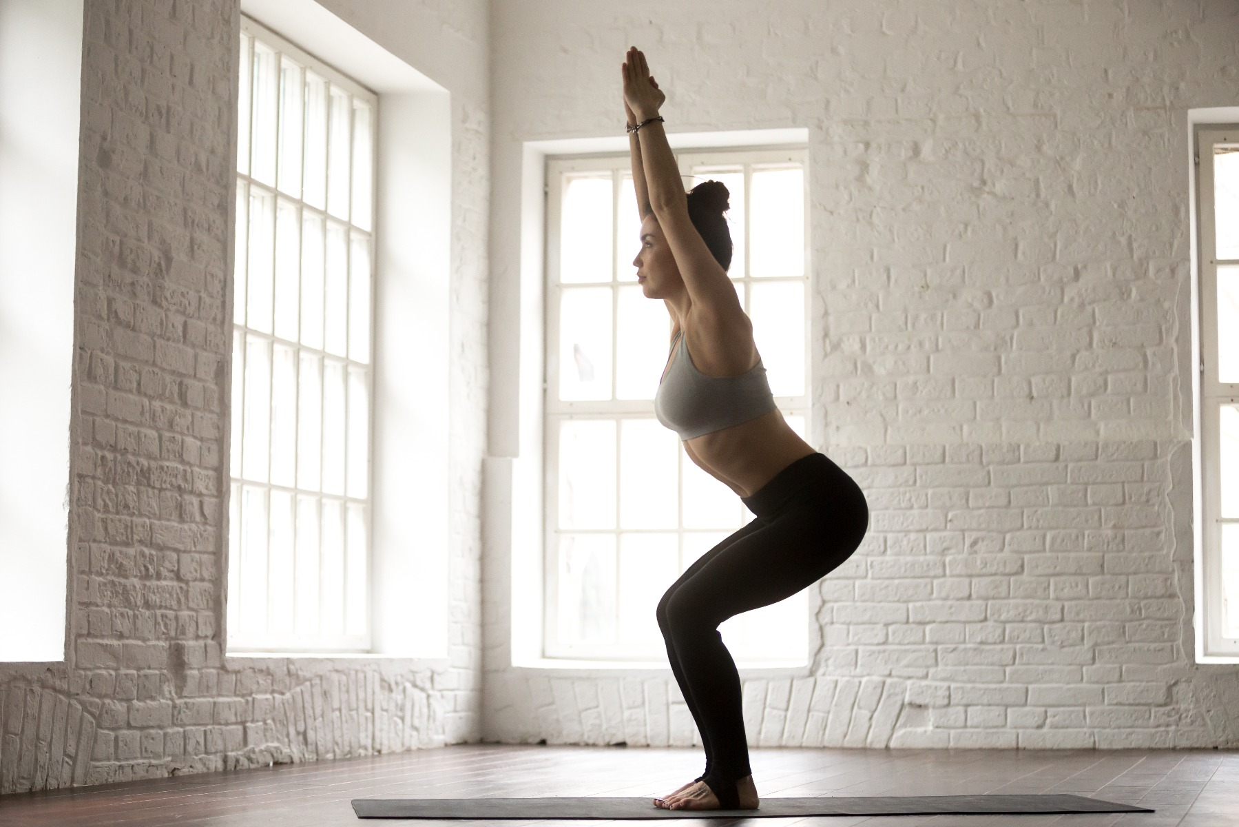 woman in yoga studio in chair pose with arms stretched overhead