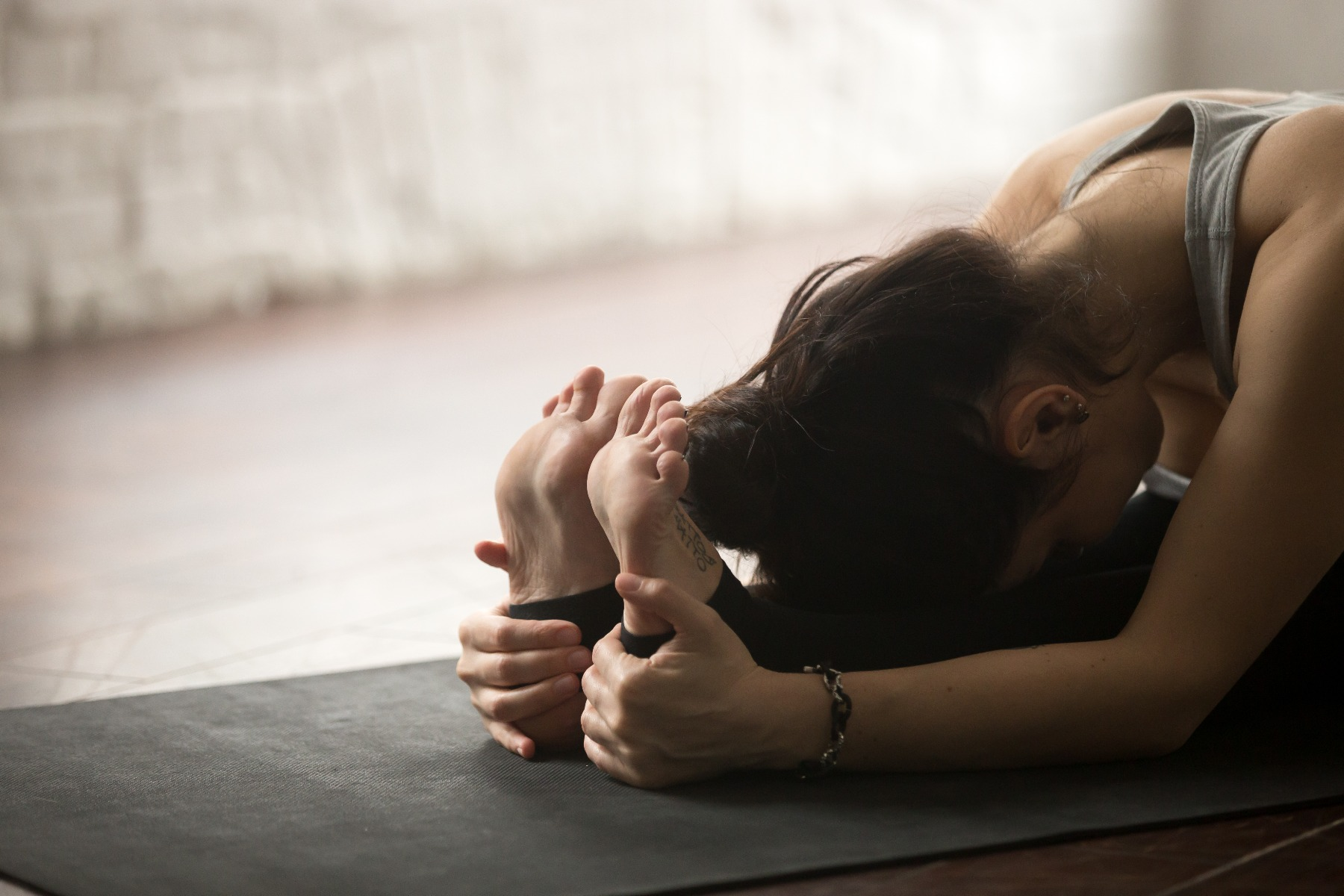 Woman practicing yoga on mat, bent over stretching to reach her toes