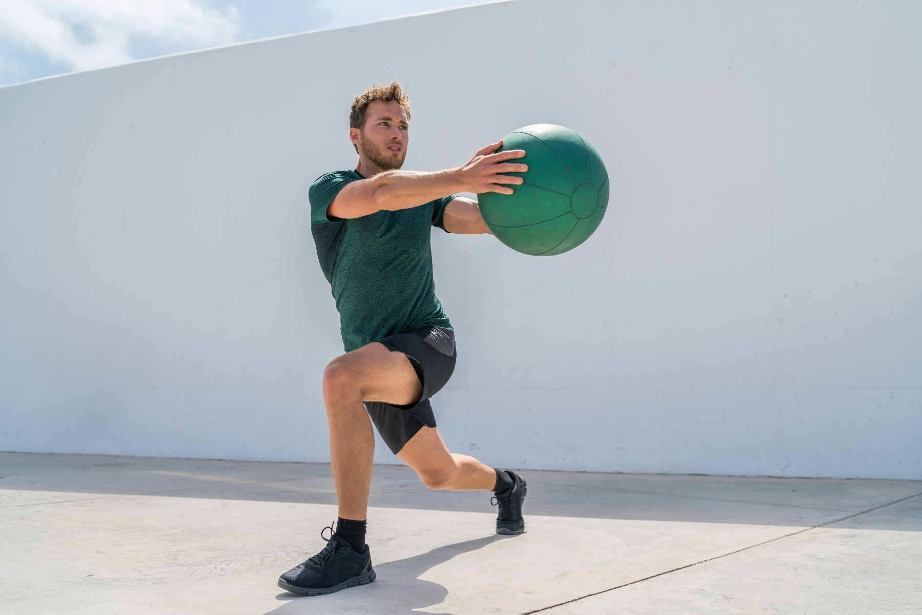 Man holding exercise ball doing twisted lunge exercise
