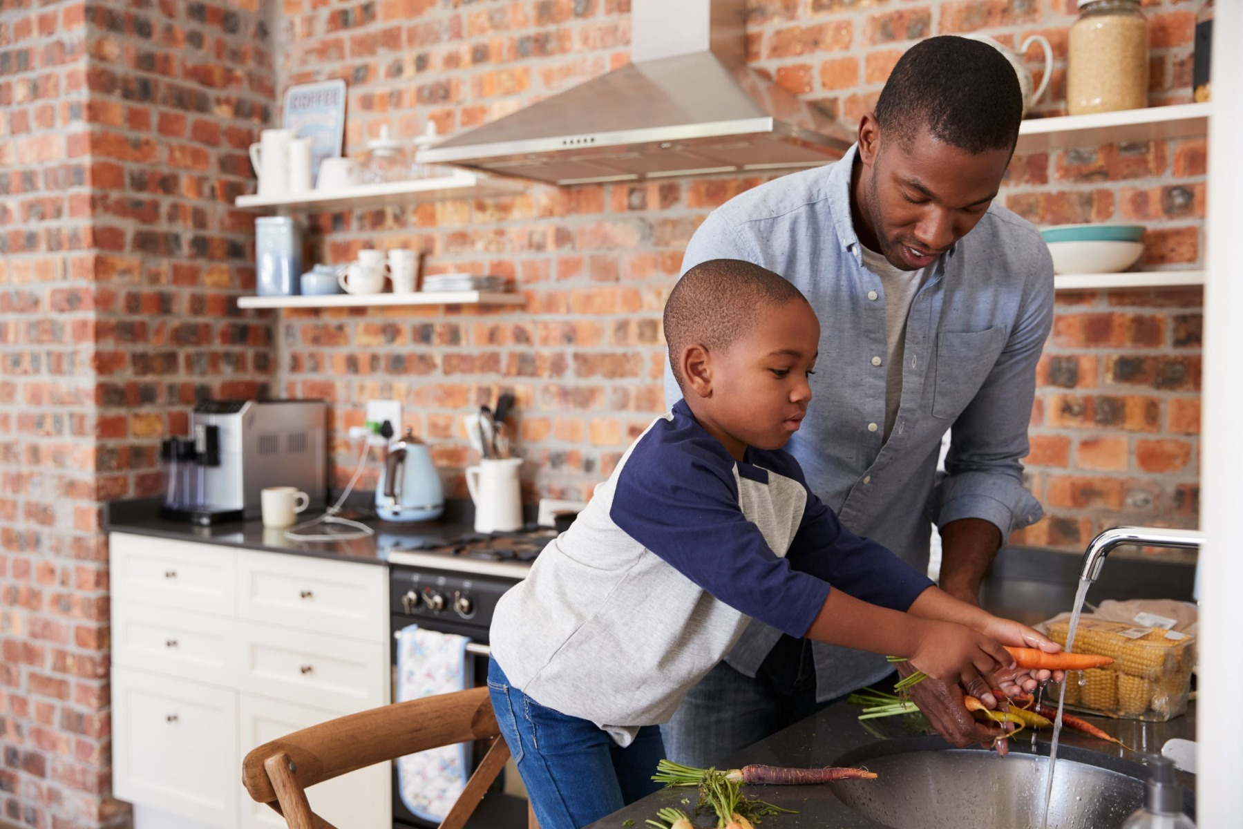 Young boy in the kitchen learning how to cook from his father