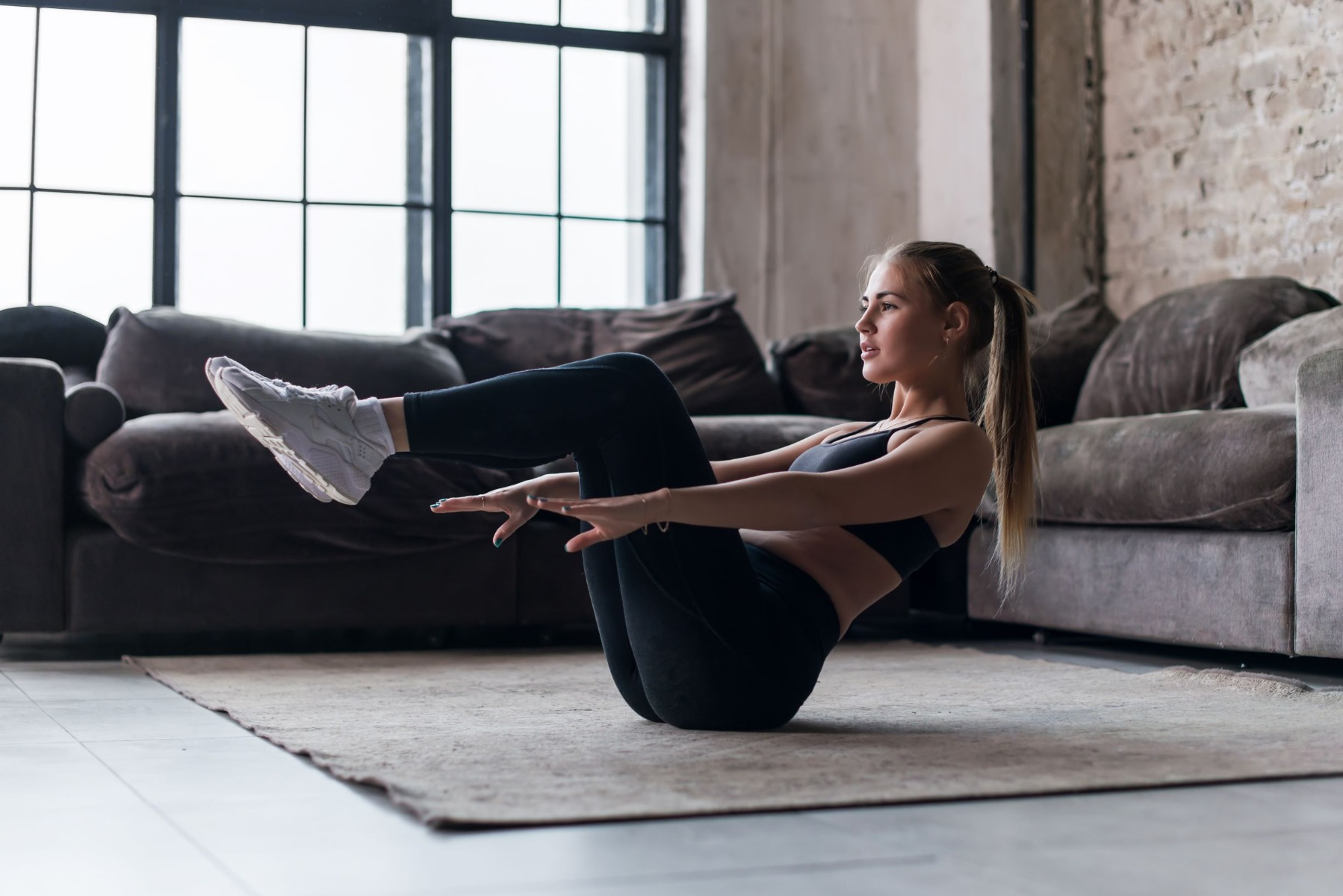 Woman on exercise mat doing V-up exercise