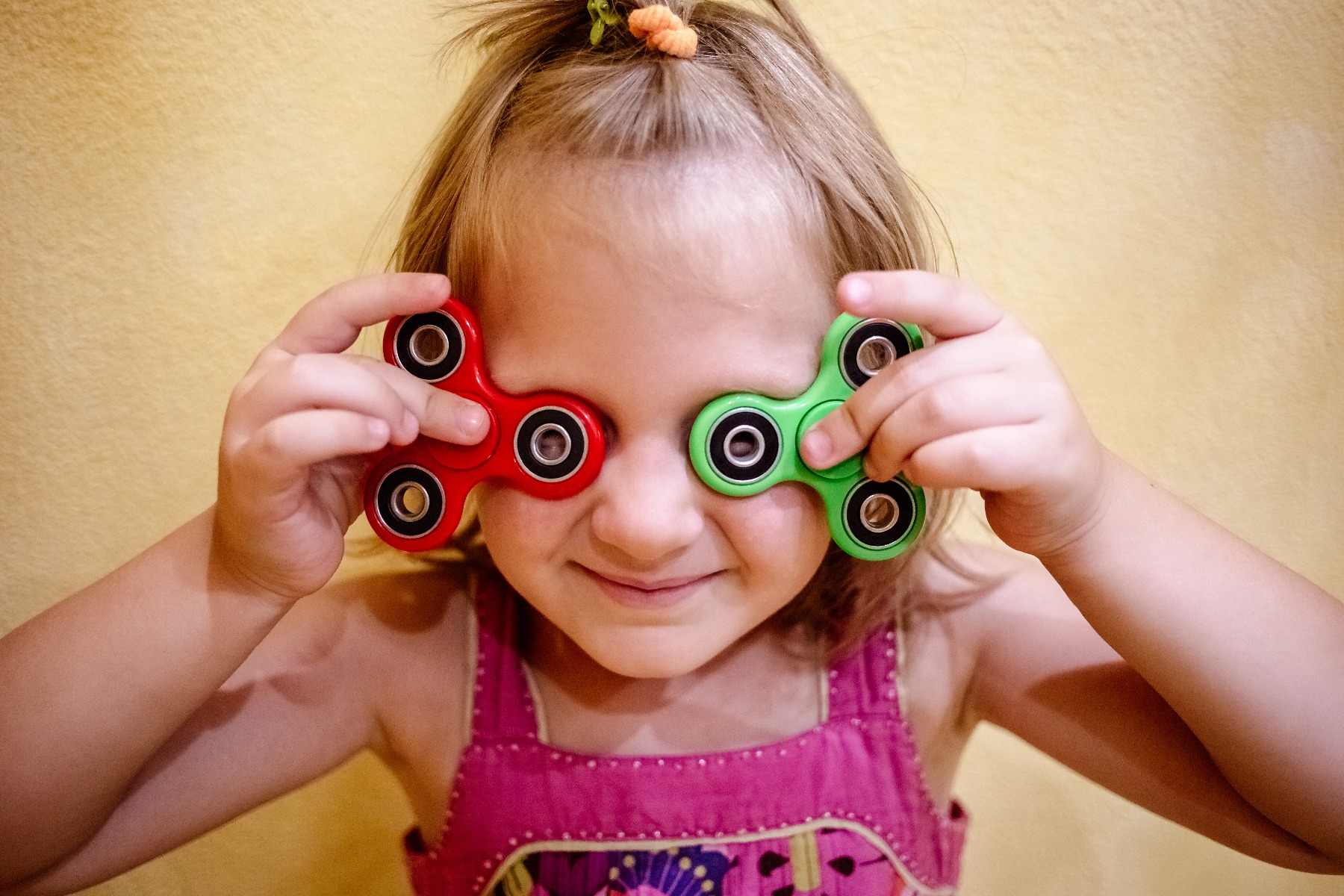 girl holding fidget spinners in front of eyes