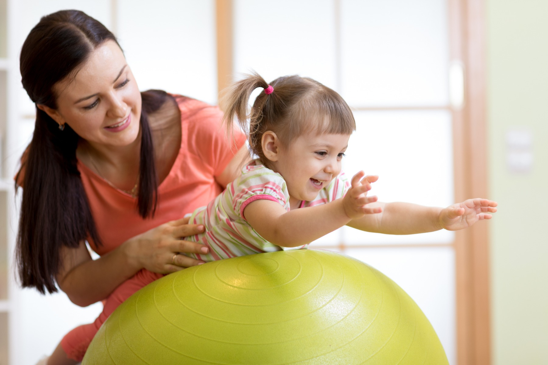 mother helping child on exercise ball