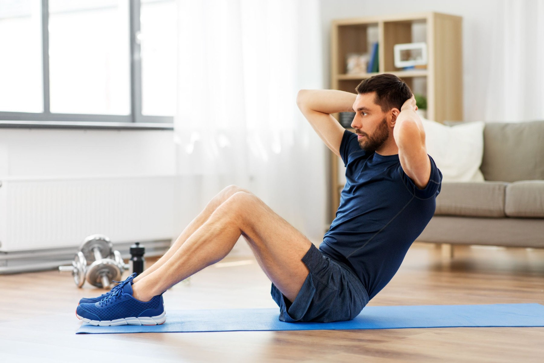 Man doing a sit-up exercise on blue exercise mat