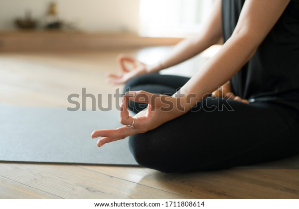 Person meditating on mat in seated yoga pose